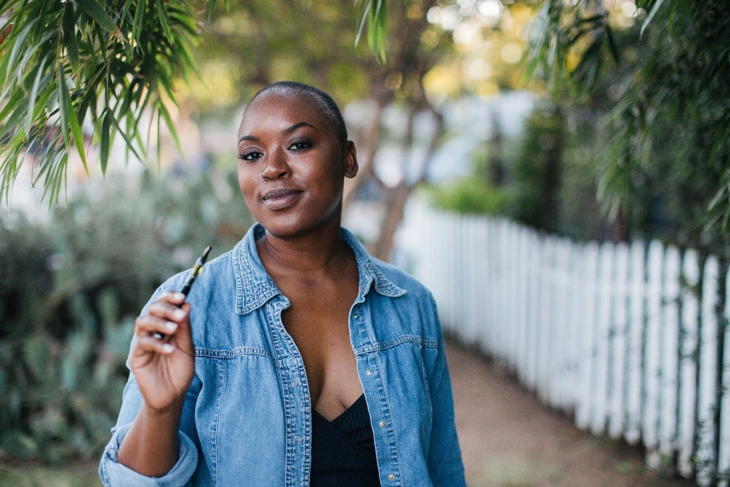 African American woman vaping CBD with an out of focus background.
